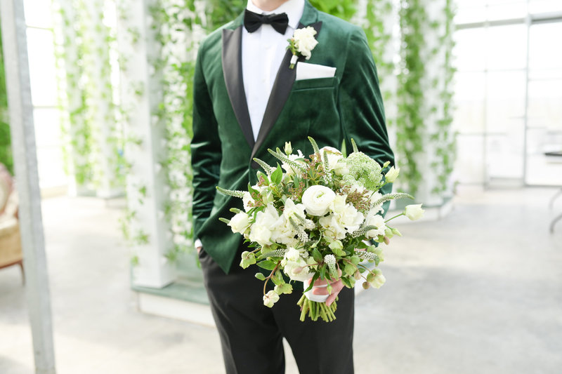 Groom in green velvet dinner jacket holds bouquet