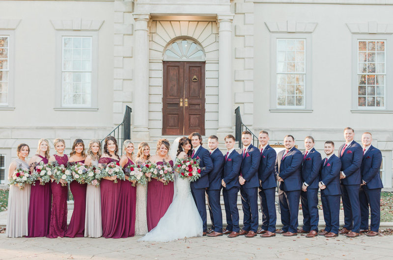 wine and navy wedding party in front of manor at great marsh estate wedding in northern virginia by costola photography