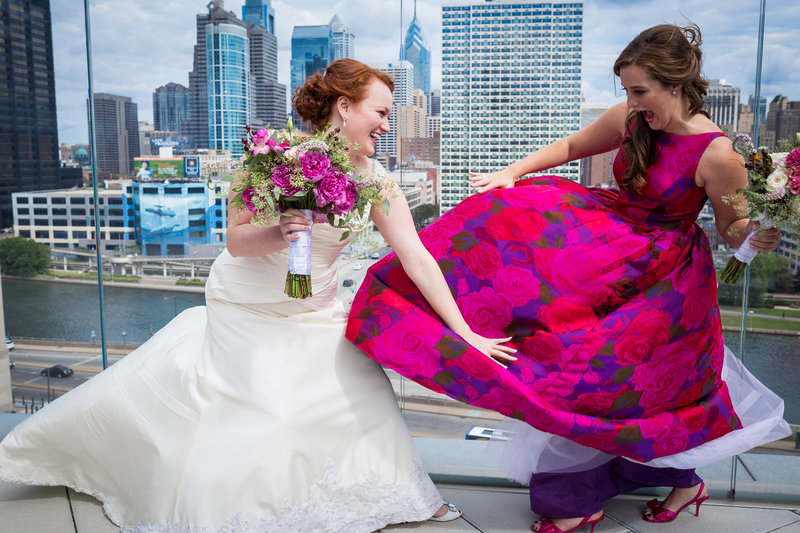Bride and made of honor laughing while holding on to the dress at Cira Green Park in Philadelphia PA