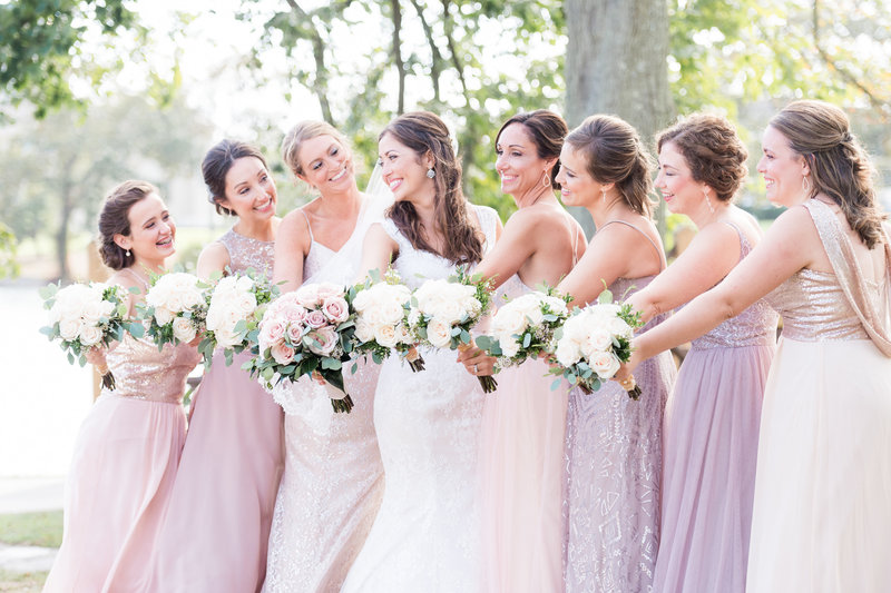 Bride and bridal party stand in a line holding bouquets