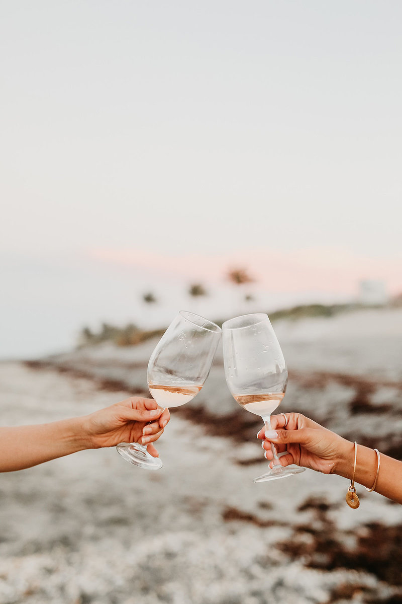 Two women clinking wine glasses in cheers on beach