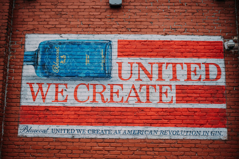 a mural featuring a bluecoat gin bottle in an american flag says united we create at philadelphia distilling company shot by philadelphia wedding photographer alex medvick