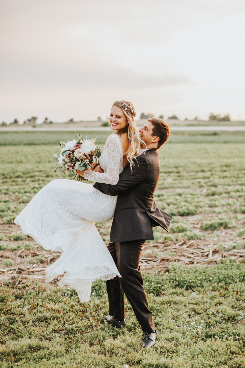 A cute, boho-styled couple hug and spin around iin an Iowa field at sunset on their wedding day.