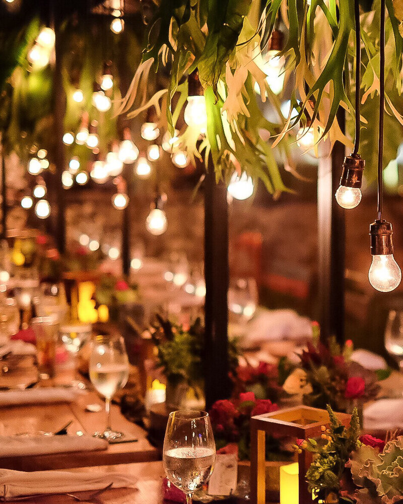 A dinner table set up for a luxury party with hanging lights and greenery outdoors.