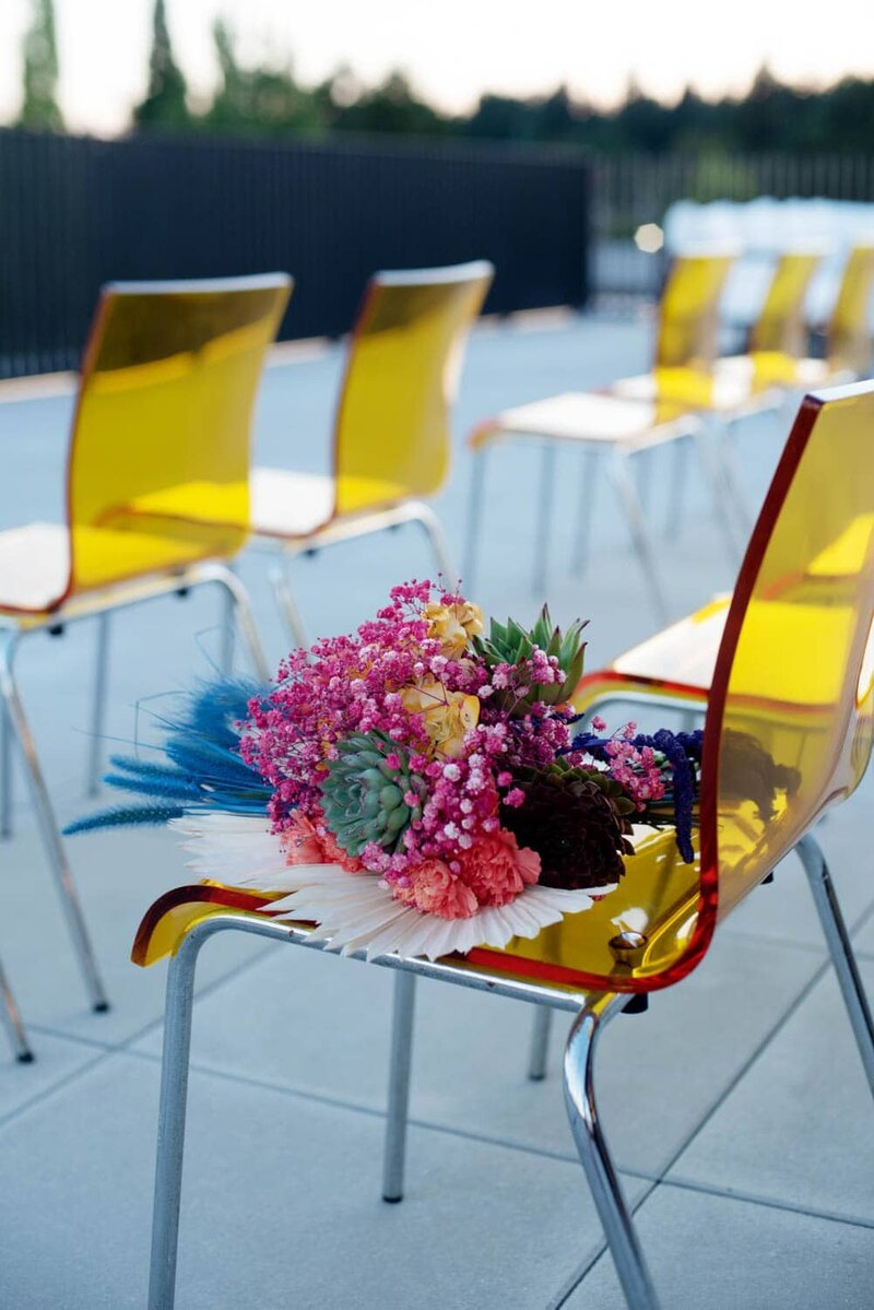 a vibrant bouquet sits on a yellow mod chair