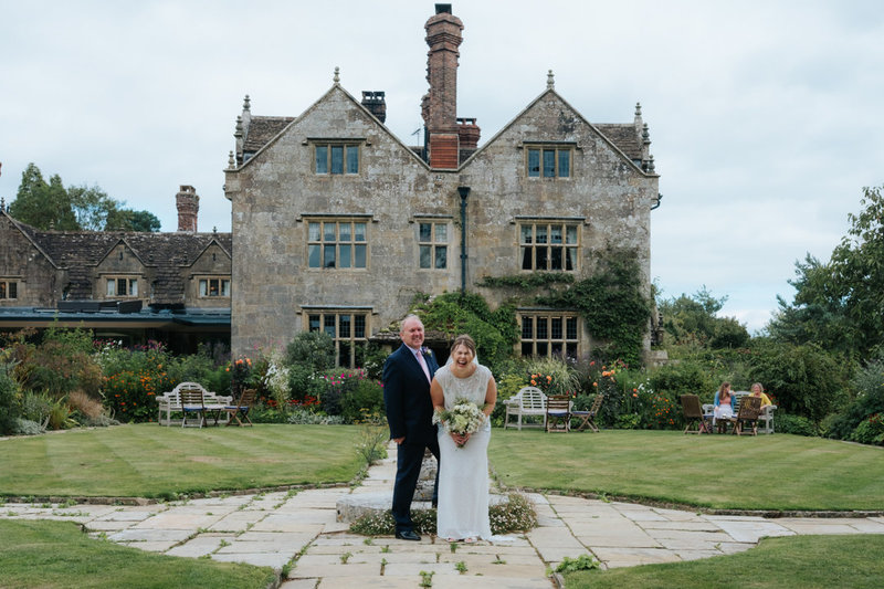Bride and her father stand together laughing on her wedding day. They stand in front of the grand and beautiful house at Gravetye Manor wedding venue
