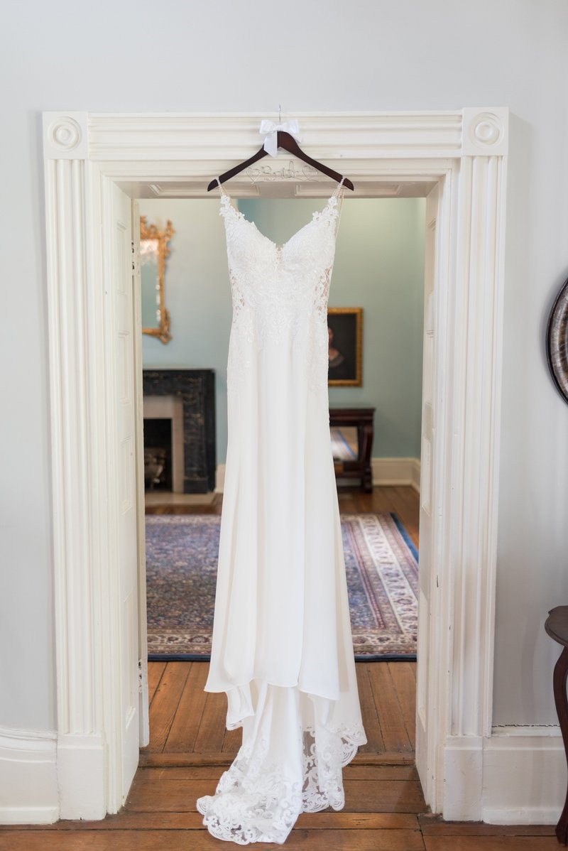 White wedding dress hanging from door at Ravenswood Mansion