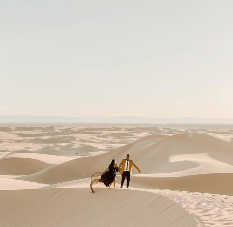 man and woman walking on the ridge of a sand dune during their glamis sand dunes elopement in california