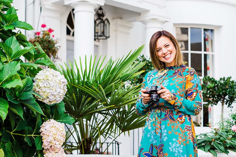 photo of charlie standing next to greenery and flowers holding her camera and looking up with a smile on her face