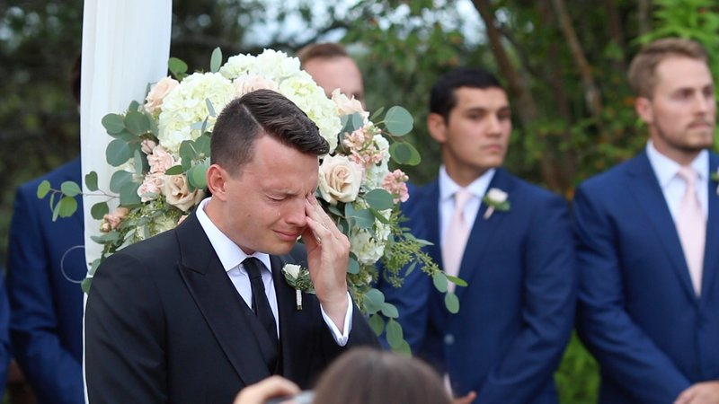 Groom wipes tears after seeing bride