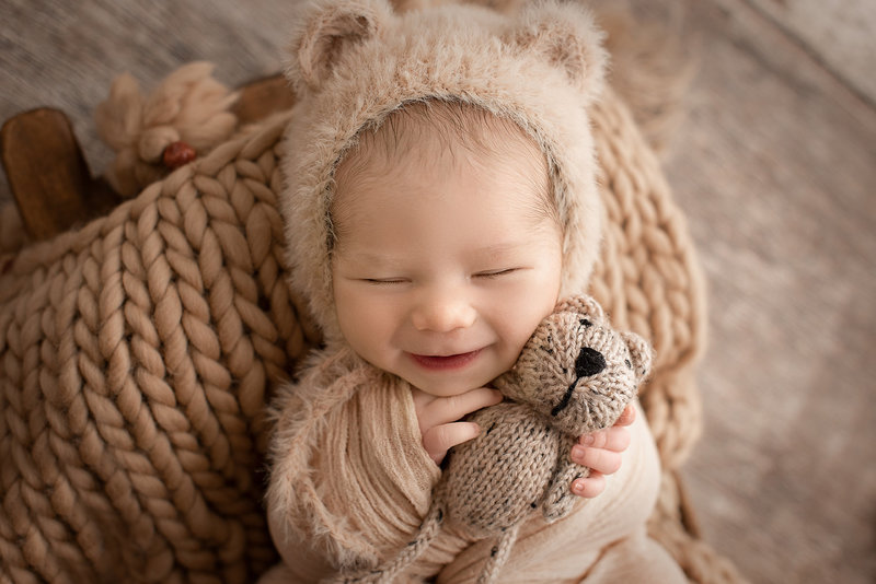 columbus ohio newborn photographer baby boy smiling with teddy bear