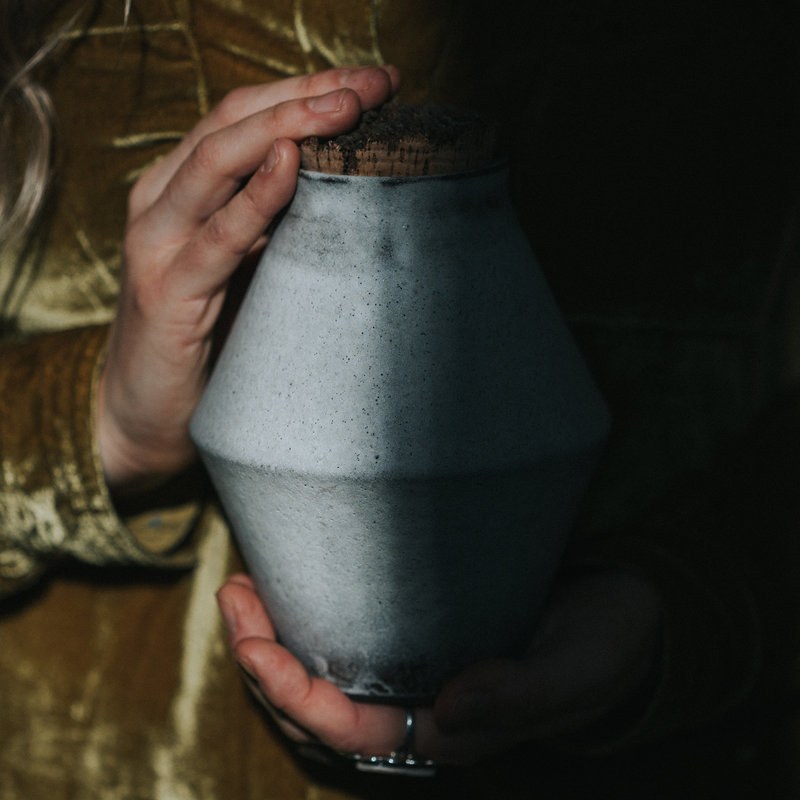 Gray handmade urn with raw cork lid being held in front of a person wearing a gold velvet shirt. Half of the photo is in the light and half is in the shadow.