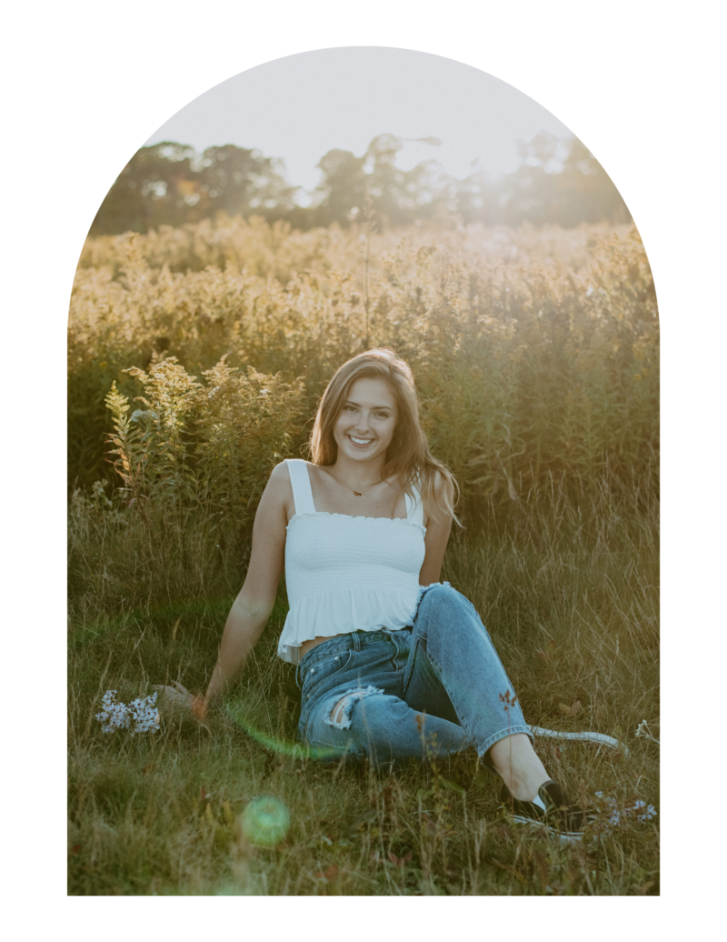 senior girl sitting in field holding wildflowers
