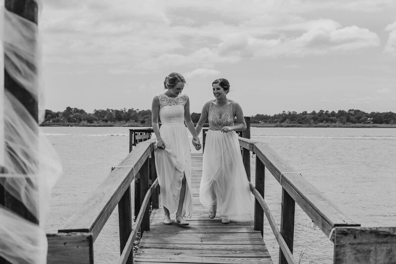Two brides walking on a dock