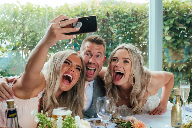 A bride, groom and bridesmaid make silly faces whilst taking a selfie at their wedding at Swallows Nest Wedding barn.