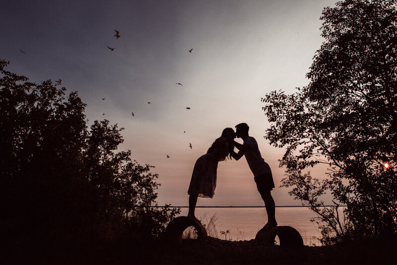 silhouette of couple leaning in and kissing with trees and birds