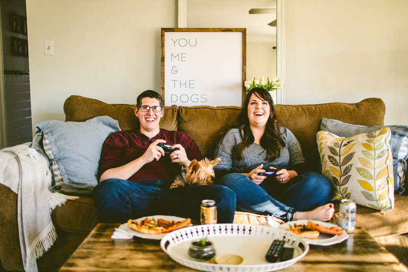 jared and rachael bowman, owners of rachael bowman photography, play video games on their couch