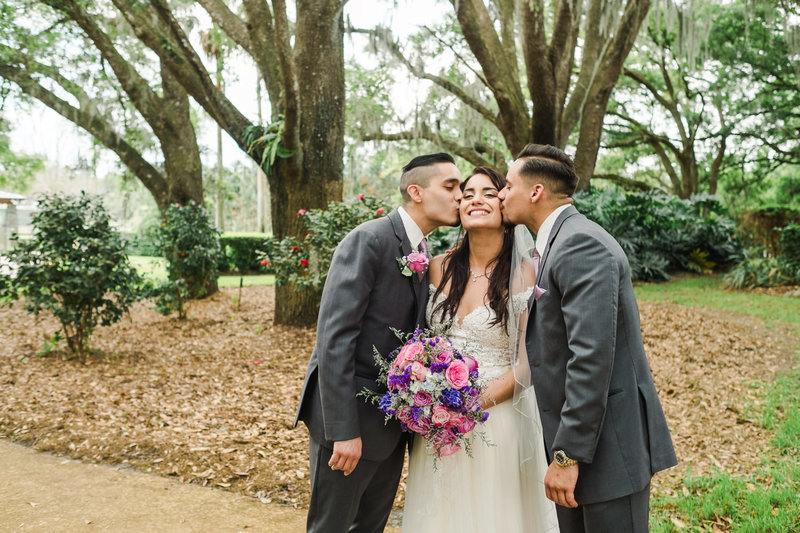 Brothers of the bride kissing her on the cheek