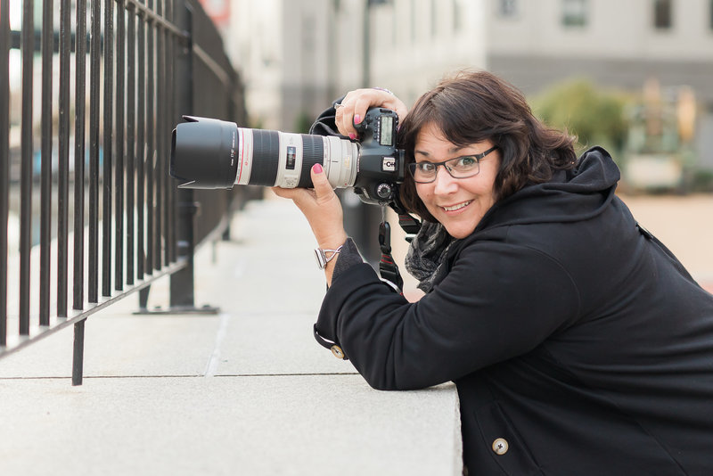 Photographer Claire Spampinato smiles from behind her camera