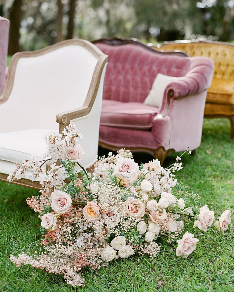 Velvet armchairs with flowers outside on the lawn