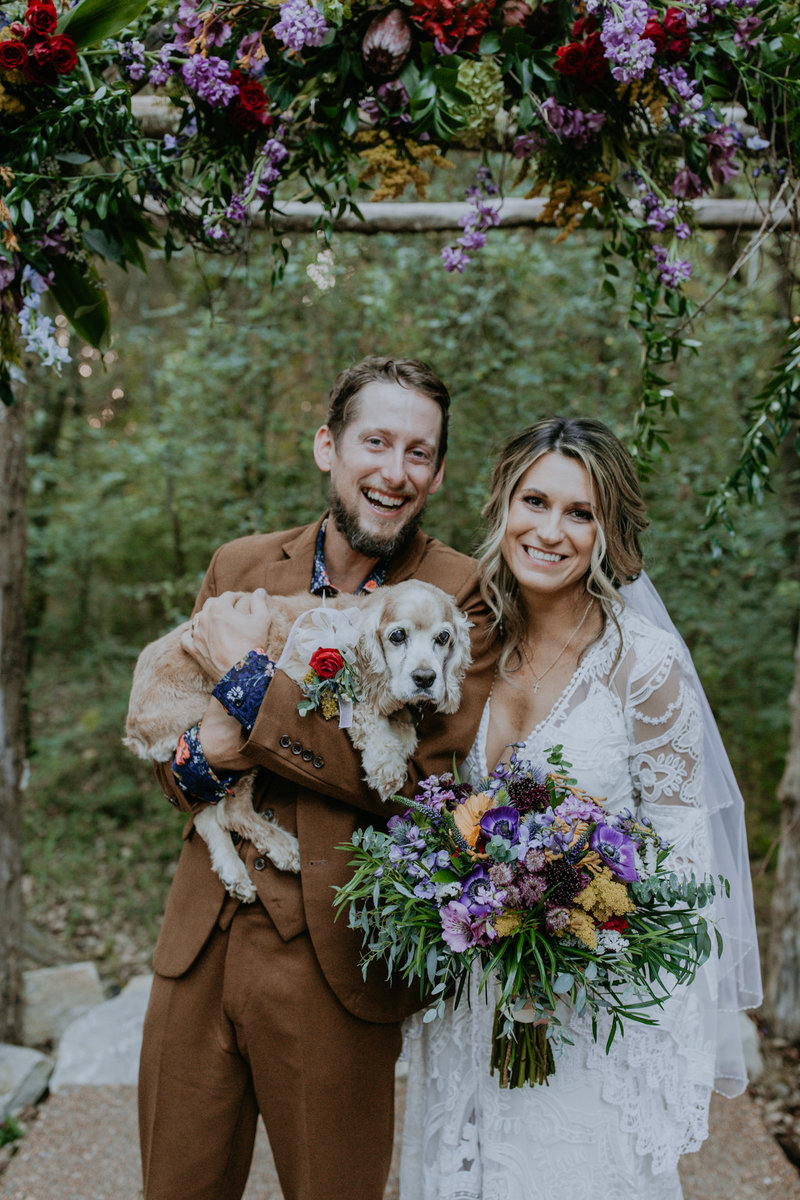 Bride and groom holding their dog under their wedding ceremony floral arch at Drakewood Farm .