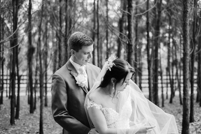 Artistic photojournalistic shot of bride and groom in black and white