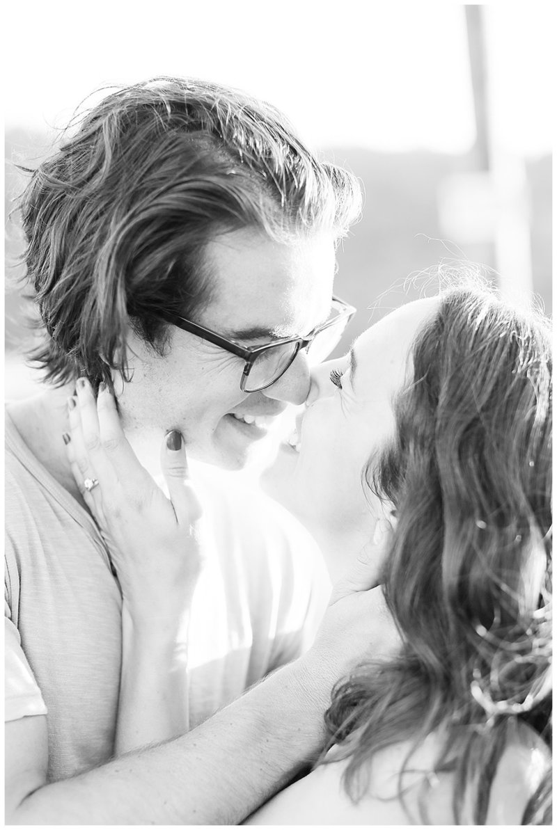 Black and white photo of couple laughing after kissing