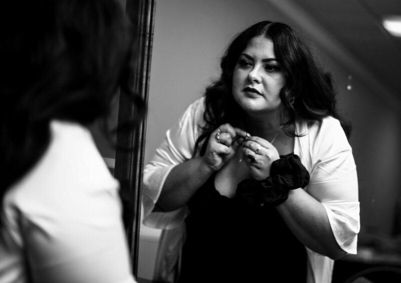 Bride adjusts her necklace in the mirror before her Halloween wedding at Peek n Peak Resort