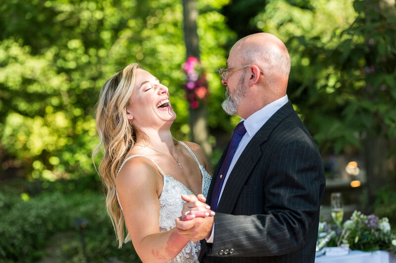 bride laughs during first dance with dad