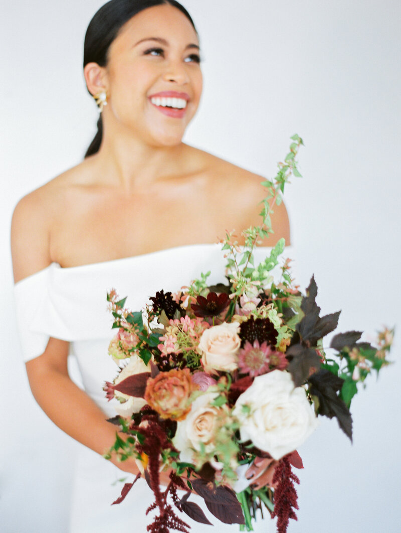 bride holding her bouquet and looking off into the distance laughing and smiling