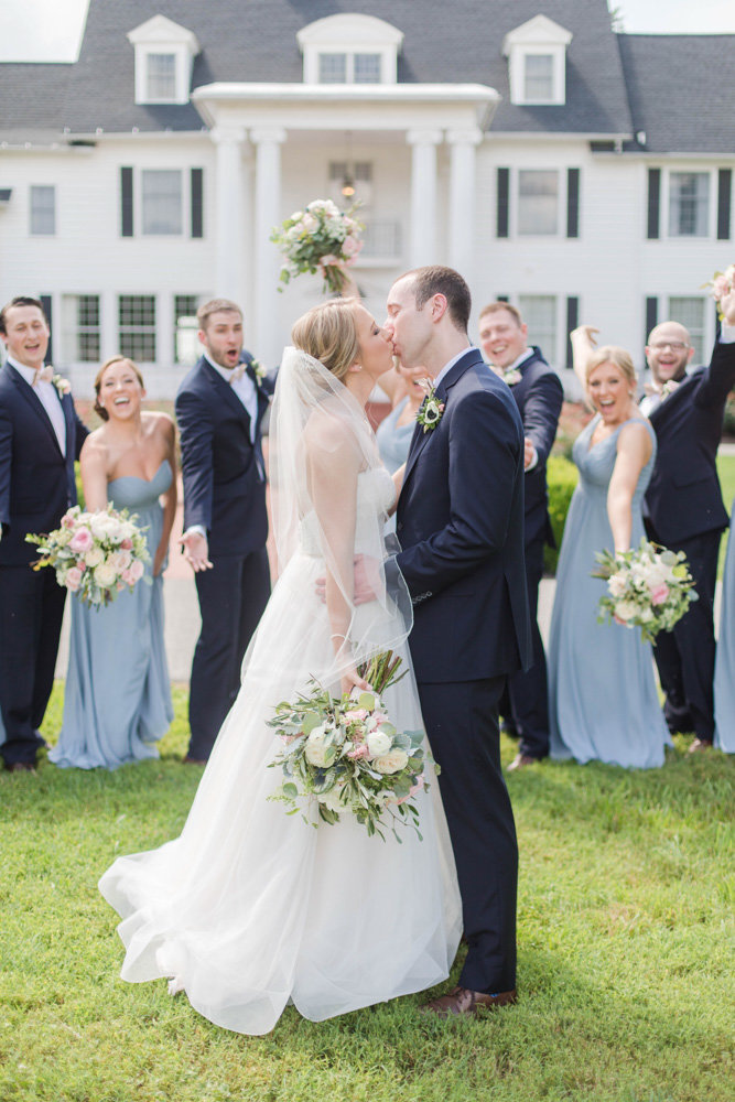 bride and groom kissing with wedding party in front of manor eastern shore wedding at kirkland manor by costola photography