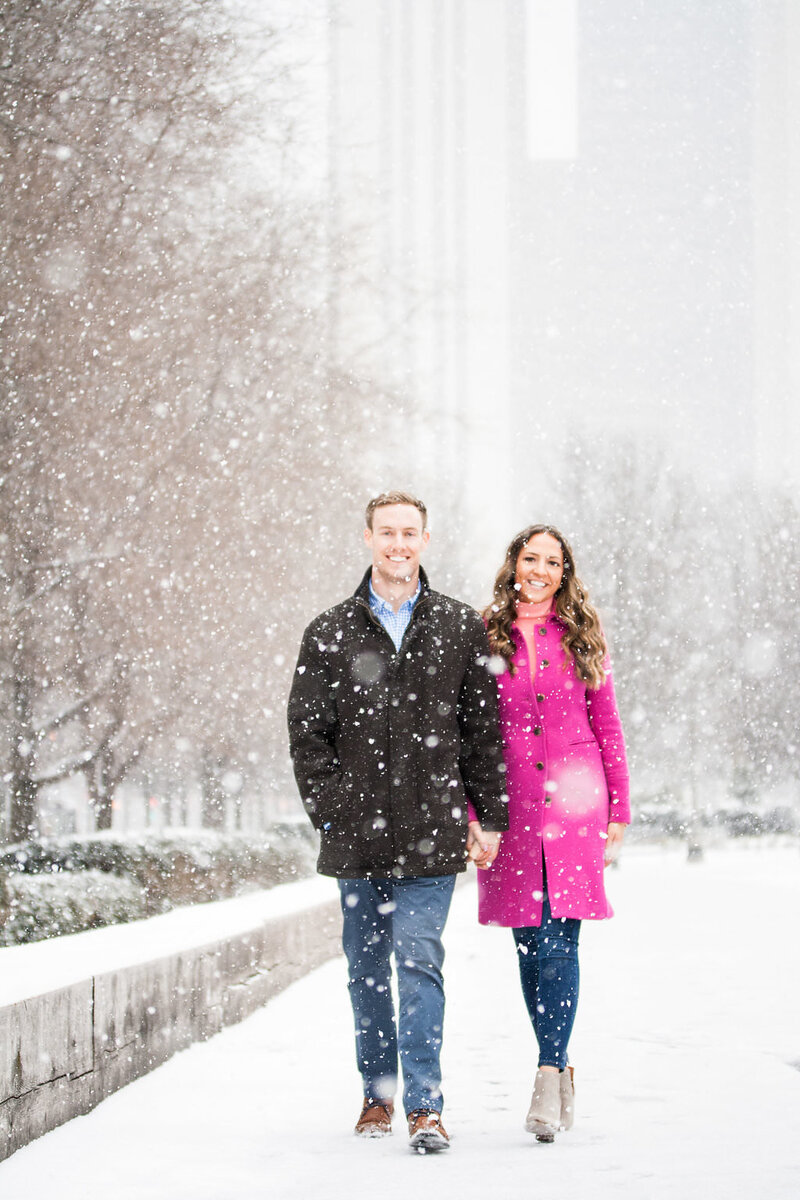 couple hold hands and walk during snowy winter engagement session in Millennium Park Chicago