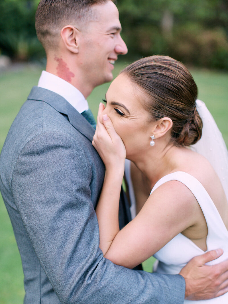 Bride covering her mouth and laughing with groom