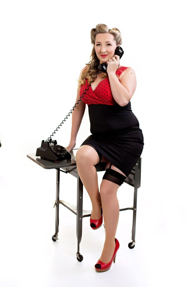 Blonde woman sitting on a vintage desk  in a red and black polka dot dress talking on a vintage phone. She is having her photo taken at Boudoir and Pinup by Janet Lynn