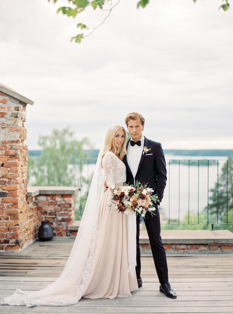 Bride in blush wedding dress from the WOW closet posing with her groom at Stockholm venue Ruin Retreat