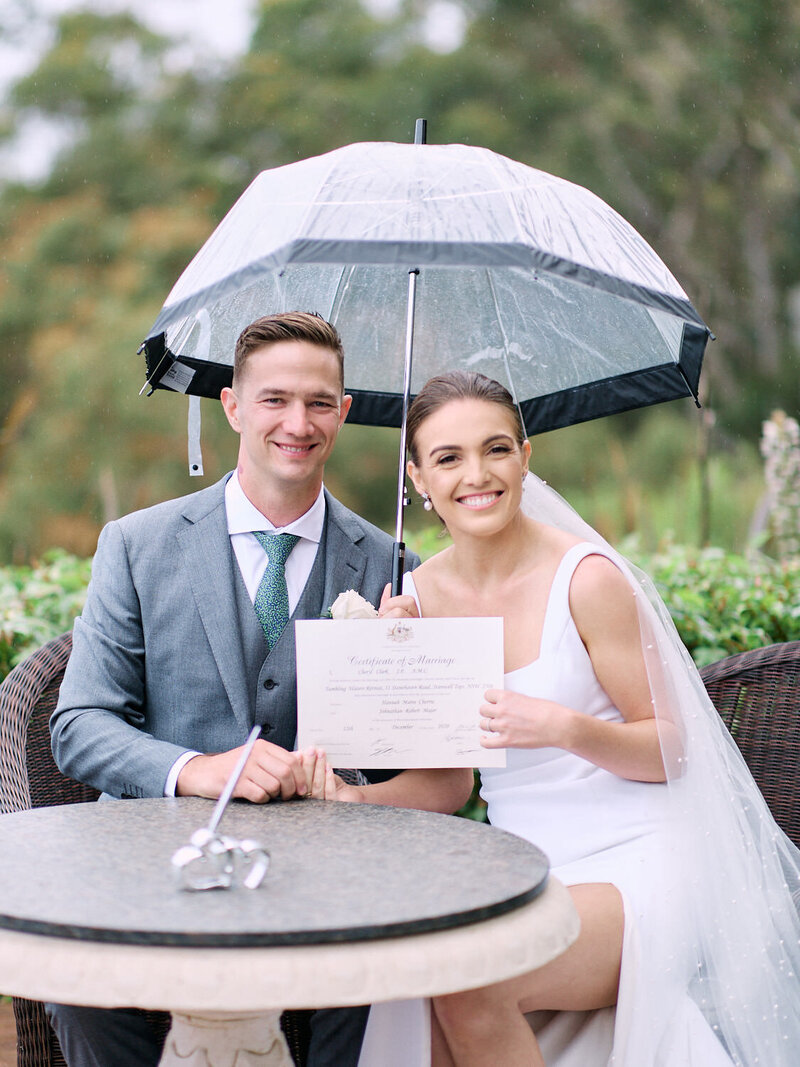 Bride and groom sitting with marriage certificate underneath umbrella