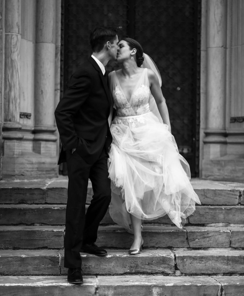 Bride and groom kiss and walk down steps of building on Yale University campus in New Haven, CT