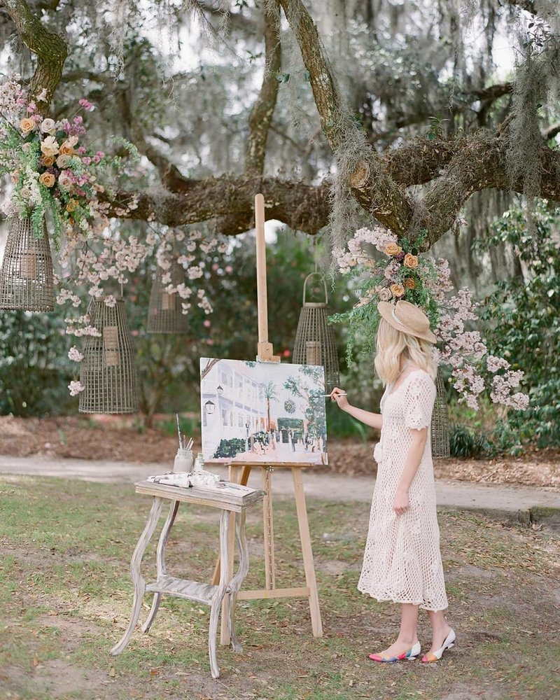 Romantic Charleston wedding ceremony with a live oak tree backdrop and live wedding painting