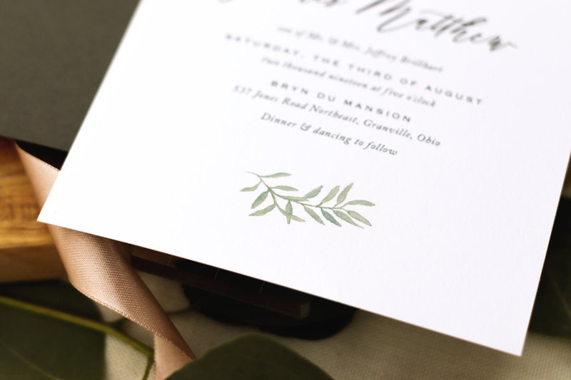 Detail Shot. A subtle watercolor eucalyptus leaf adorns the bottom of the invitation. Paired with beautiful typography and modern calligraphy, this invitation is perfect for any wedding.