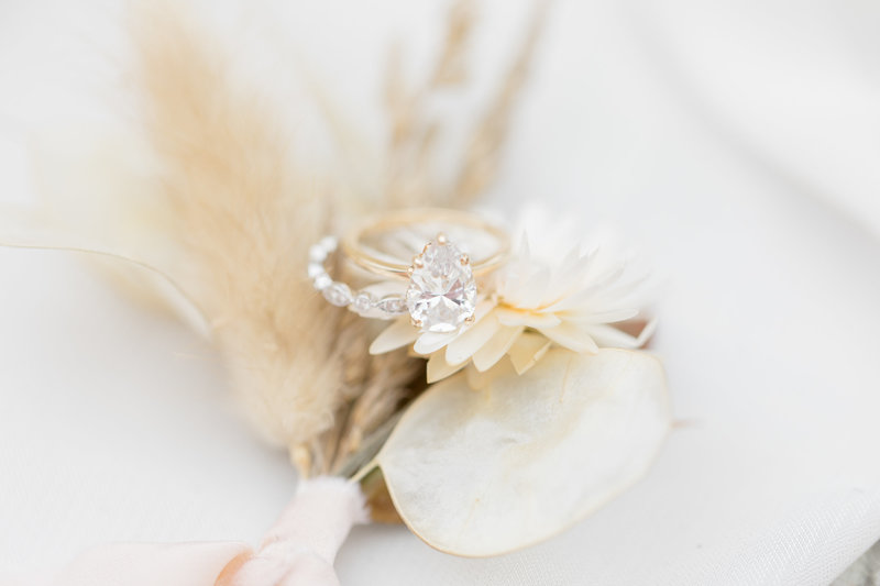 wedding ring on top of white flowers by photographer