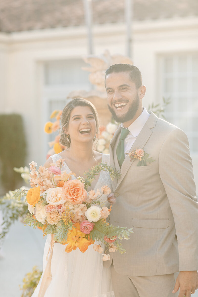 Bride and groom smile brightly while holding multi-colored bouquet