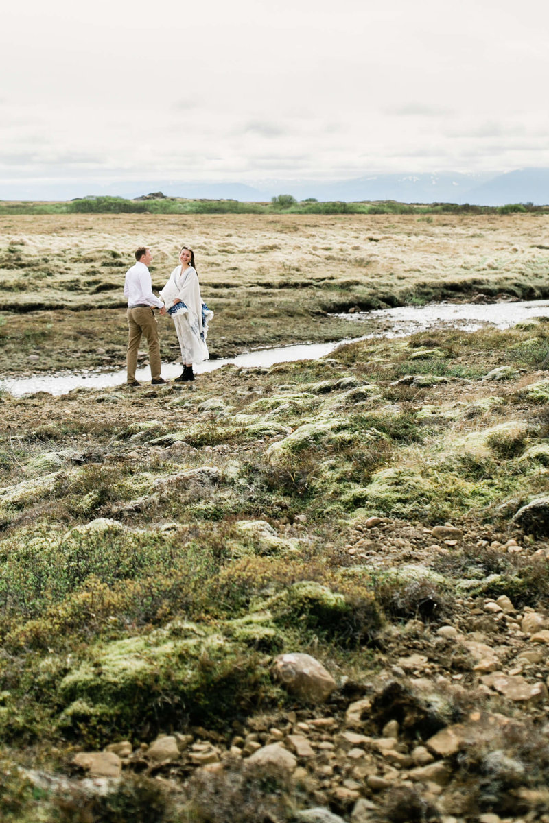 the couple hands beside  a river in iceland during their elopement