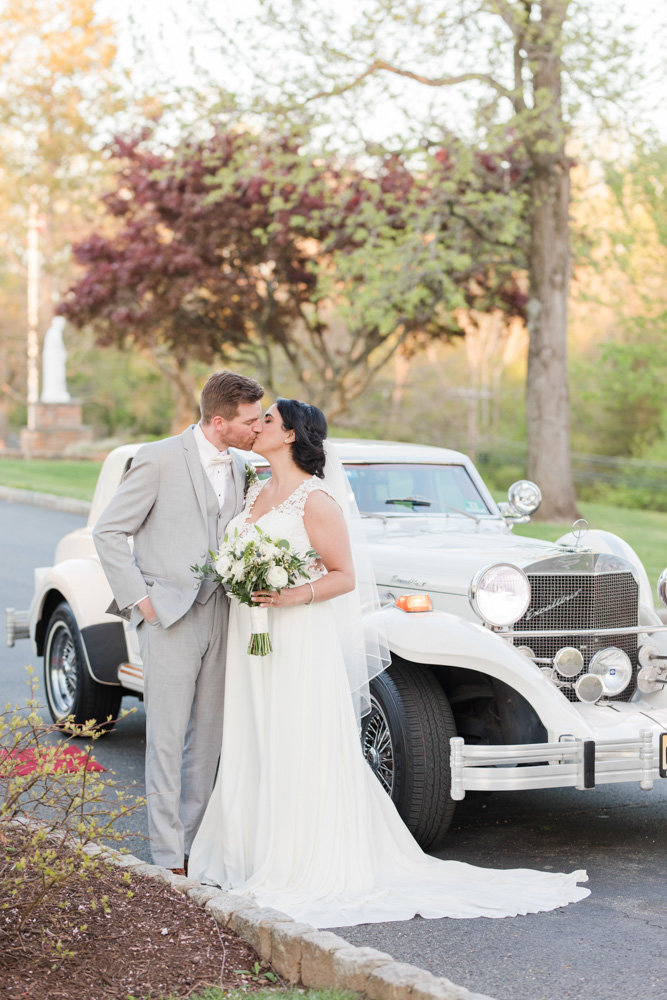 bride and groom kissing by old white car  at Stone House at Stirling Ridge Maryland Wedding by  Costola Photography