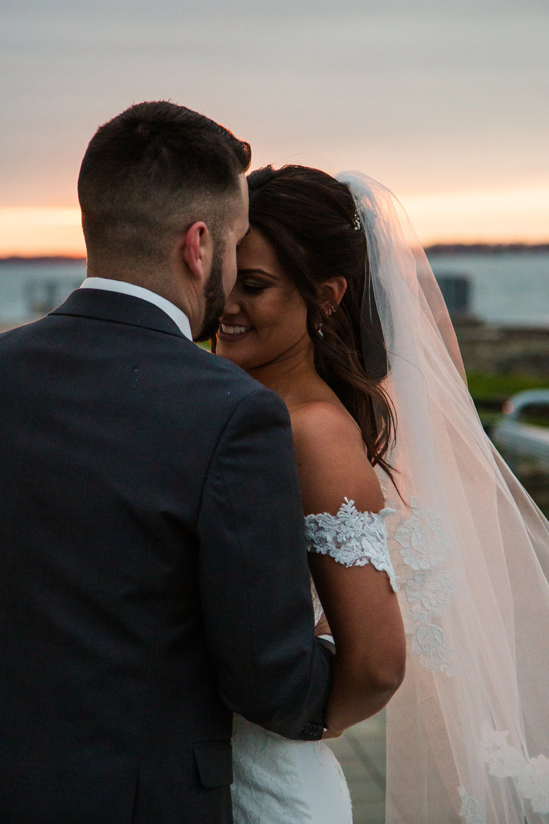 Groom pulls smiling bride close to him at sunset outside the Sheraton Erie Bayfront Hotel