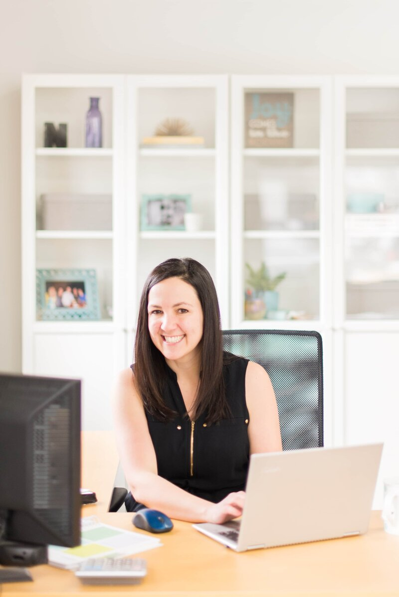 Woman with brown hair dressed in black sitting on a black chair with a laptop in front of her on a wooden top desk