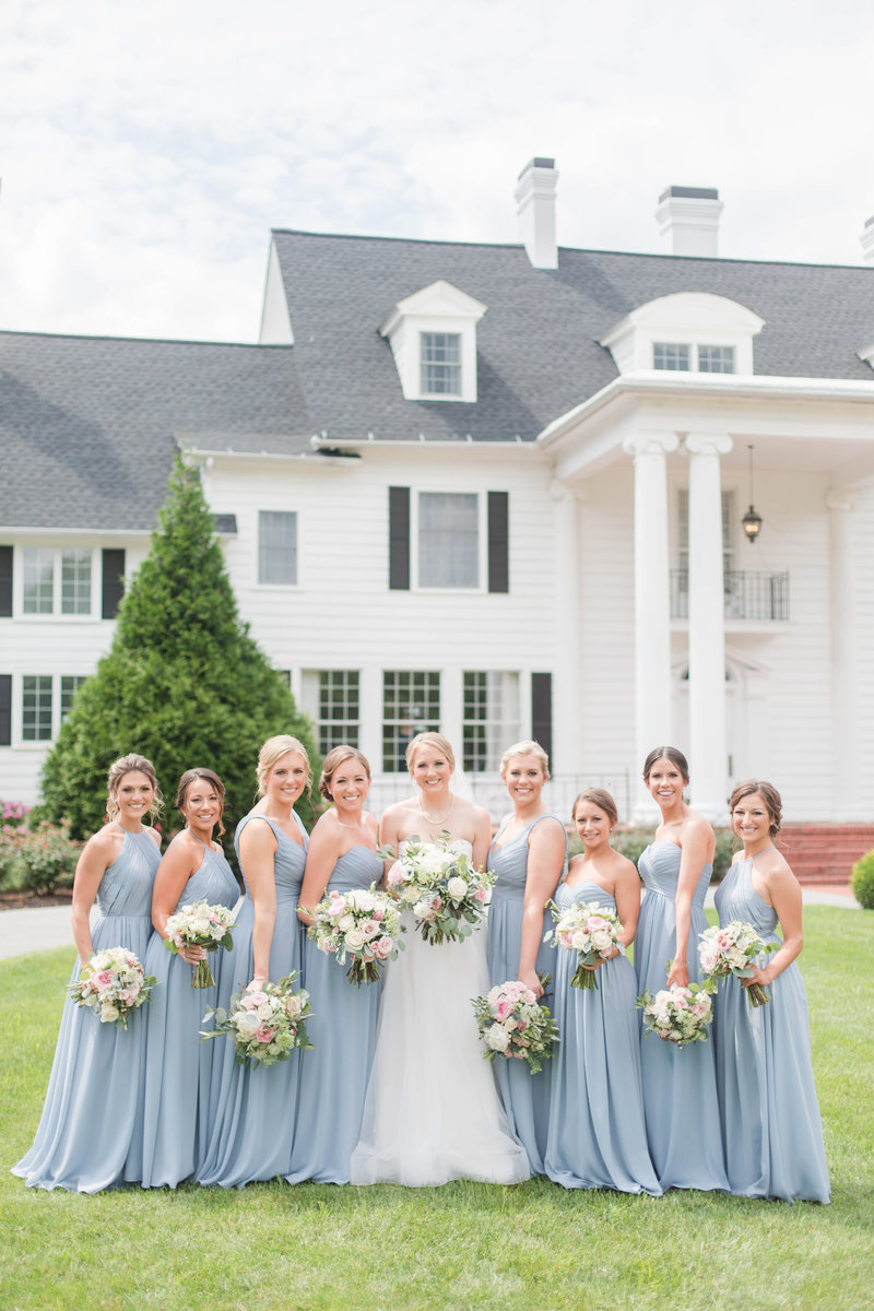 bridesmaids standing in blue dresses in front of kirkland manor on eastern shore maryland st michaels by costola photography