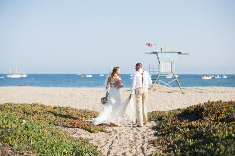Bride and groom walk on beaches of Santa Barbara after wedding