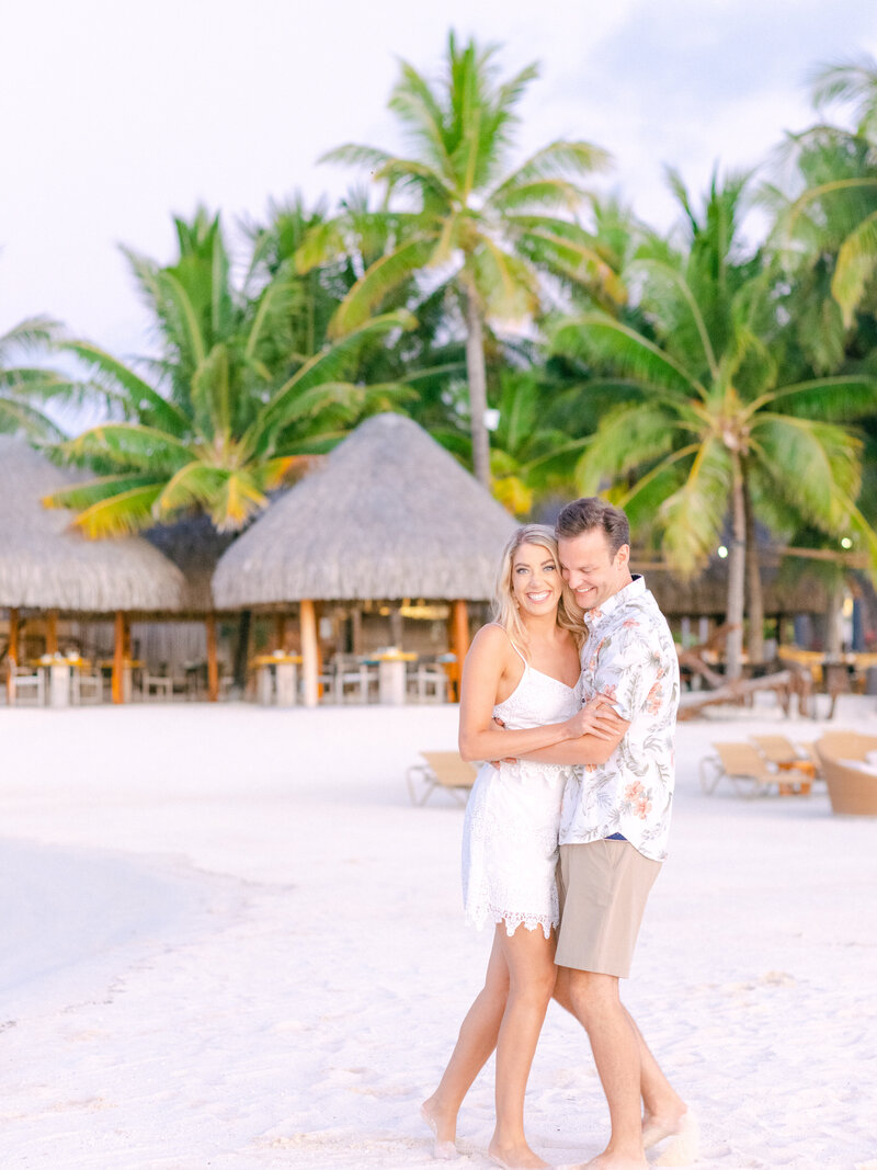 Couple walking playing at sunset in the Four seasons bora bora on the beach