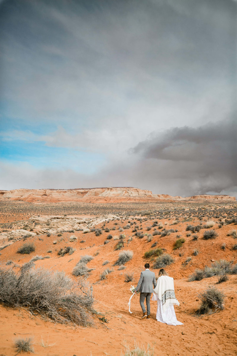 With a storm in the distance the couple walks into the open desert during their elopement.
