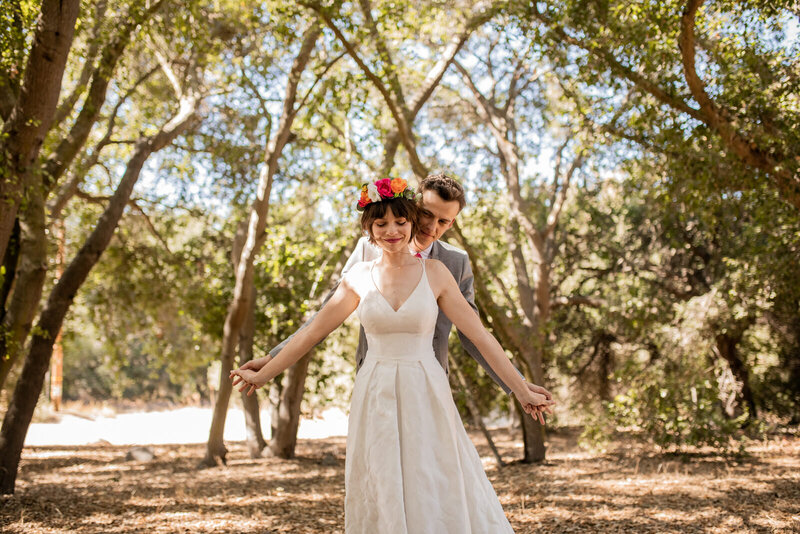 Bride and groom holding hands in the middle of  a forest
